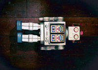 retro silver robot toy lying on  a old wooden floor