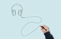 man using black marker to draw headphones with a single line