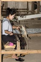 Junge Frau webt an einem traditionellen Lao-Thai Webstuhl