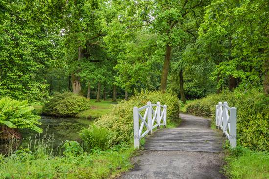 White wooden bridge in Luetetsburg castle garden, East Frisia, Lower Saxony, Germany