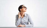 Confident businesswoman in glasses sitting at desk