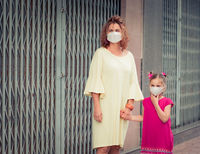 Woman and daughter wearing facial disposable mask. Coronavirus protection