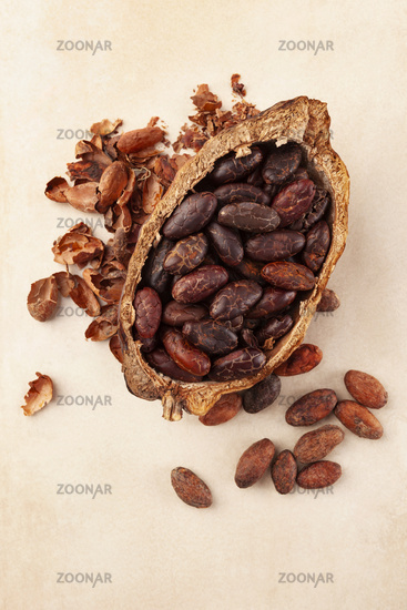 Fresh peeled cocoa beans in pod on beige background.