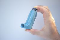 A person holding an asthma inhaler on a clear background