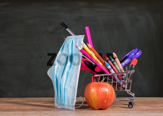 Back to school concept with pencils, crayons in shopping cart with apple with face mask