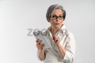 Thoughtfully businesswoman holds white tablet computer. Cheerful Caucasian model in white blouse posing on white background. Bright female portrait in high key