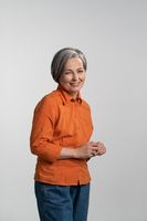 Middle aged grey haired pretty woman smile gentle looking at camera with touching finger tips wearing orange shirt and denim jeans isolated on white background. Human emotions concept