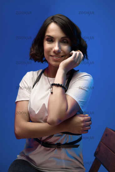 Smiling woman wearing white t-shirt touching her cheek with hand posing on blue background in studio