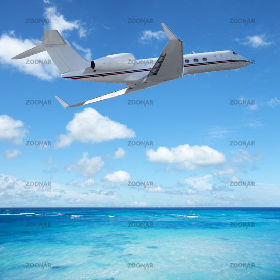 Private jet plane over the tropical sea