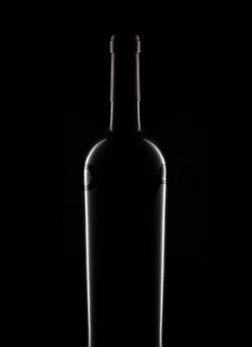 Closeup silhouette of a bottle of red wine over a black background.