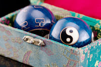 Blue Qigong balls with white yin and yang symbols in a green box