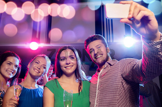 friends with glasses and smartphone in club