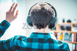 Enjoying music at home: Young Caucasian man is listening to music with headphones. Blue checked shirt.