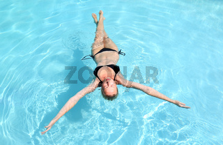 Beautiful Caucasian lady floating in swimming pool.