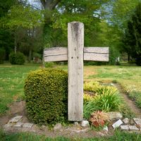 Cross made of wood on a grave in the cemetery