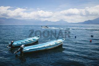 Two blue boats on lake Atitlan with view on volcanic mountians in Santa Cruz la Laguna, Guatemala