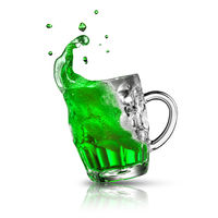 Green alcoholic drink splash in a beer mug on a white.