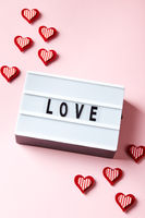 Love lightbox message with red hearts on pink background.