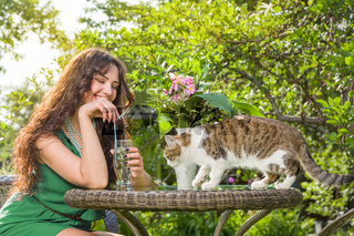 Young woman with cat at backyard at sunny day