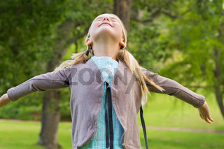 Girl with arms outstretched looking upwards at park