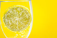 Fresh cut lemon in soda water glass with bubble on yellow background. Healthy commercial fruit photography.