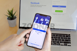 Calgary, Alberta. Canada. Nov 11 2020: A close up of a person using Facebook app on an iPhone Pro 12 and Macbook Pro on a wooden table with a plant.