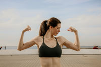 Headshot of young sporty woman showing biceps posing outdoor.