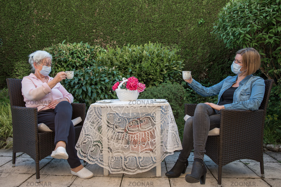 Senior woman and daughter with face masks having coffee in the garden at safeteyl distance