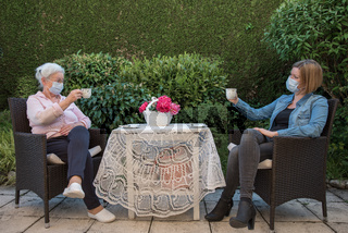 Mutter und Tochter mit Mundschutz trinken Kaffee im Garten
