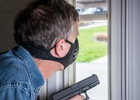 Senior man with face mask peering through front door window with gun during quarantine