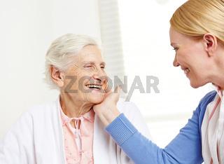 Tochter streichelt alte Mutter über Wange