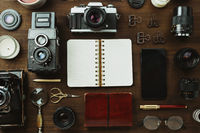Vintage film camera, lenses and stationery on dark wooden table, rustic flatlay