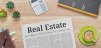A newspaper on a desk with the headline Real Estate