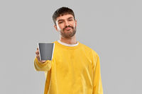 displeased young man with coffee cup