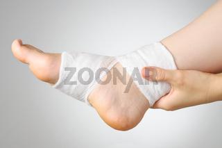 Injured painful foot with white gauze bandage