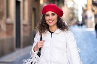 Happy woman walking on the street with red hat and happy
