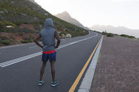 Fit african american man in sportswear standing on a coastal road