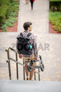 Young caucasian man in casual clothes with a backpack carries a folded electric scooter in his hand up the stairs of an office building. Man Carrying E-Scooter in folded position From Work