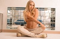 Playful blonde sitting in front of glass decor