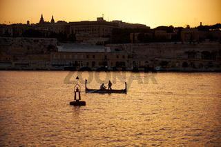 The early morning view of two people sailing  in a traditional Maltese boat along the Grand harbor. Malta
