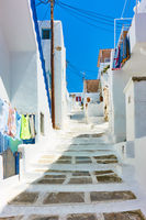 Uphill street with old white houses in Mykonos