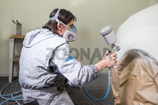 Car body painter spraying paint on bodywork parts