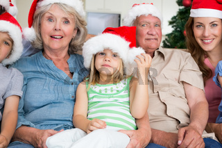 Happy multigeneration family wearing santa hats on the couch