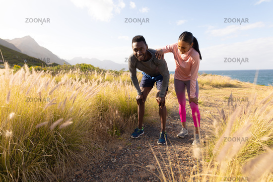 Fit african american couple in sportswear resting leaning on knees in tall grass