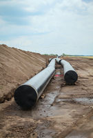 Pipes for a new pipeline for the water supply lie in a field.