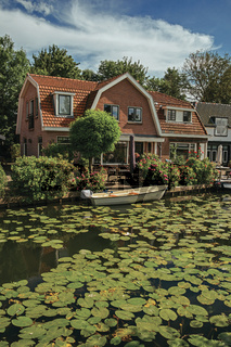 Canal with aquatic plants, boats and brick houses in Weesp