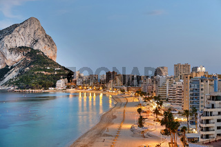 Panoramic view from above of Calpe cityscape. Street lights illuminating seafront promenade during sunset. Empty sandy beach and rocky mountain of Penon de Ifach. Costa Blanca Alicante province, Spain
