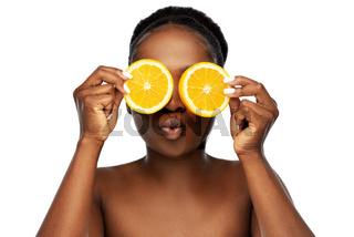 african woman making eye mask of oranges