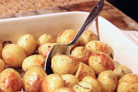 Roasted baby potatoes out of the oven with a spoon