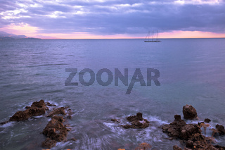 Sailboat on French riviera coast on moody sunset view